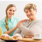caregiver and elderly patient sitting at a wooden table with cup of coffee